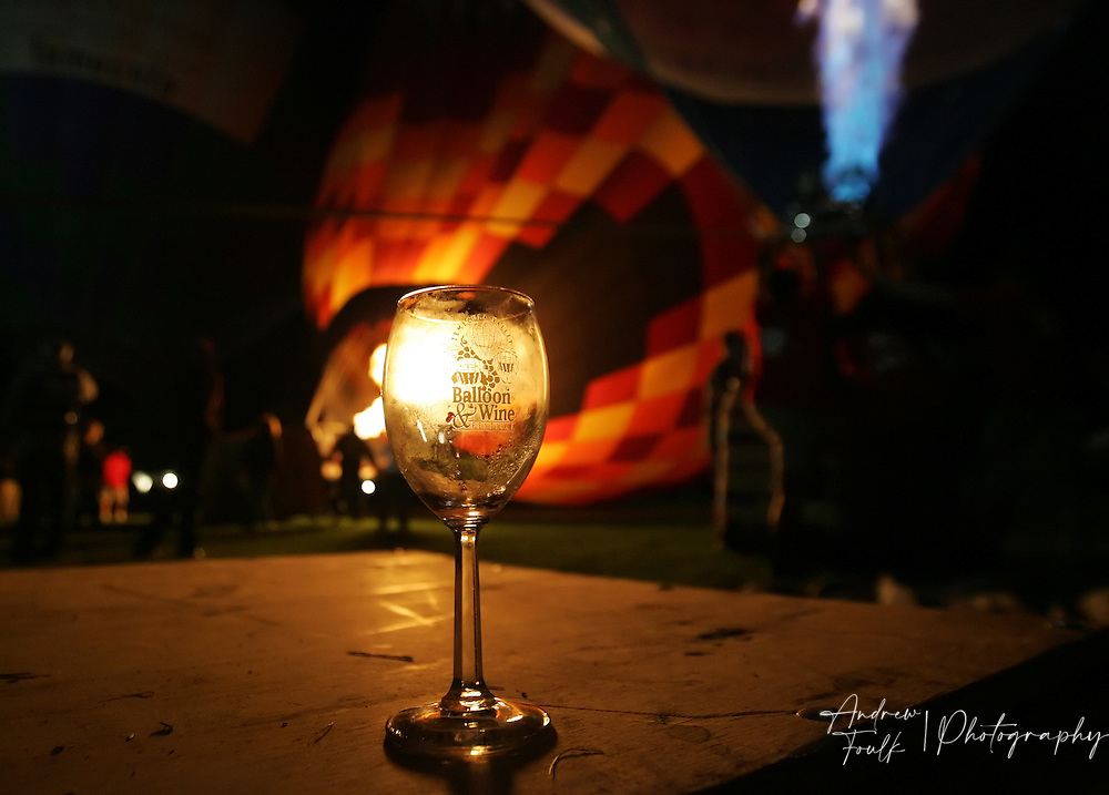 /Andrew Foulk/ For The Californian/.An empty wine glass sits on a trailer as hot air balloons are filled during the Balloon Glow part of the 26th annual Temecula Balloon and Wine festival.