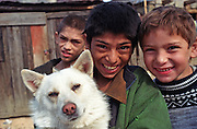 Jarovnice/Slovak Republic, Slovakia, SVK, 06.08.2003: Roma children with a dog in JAROVNICE - the biggest Roma Settlement in eastern Slovakia.