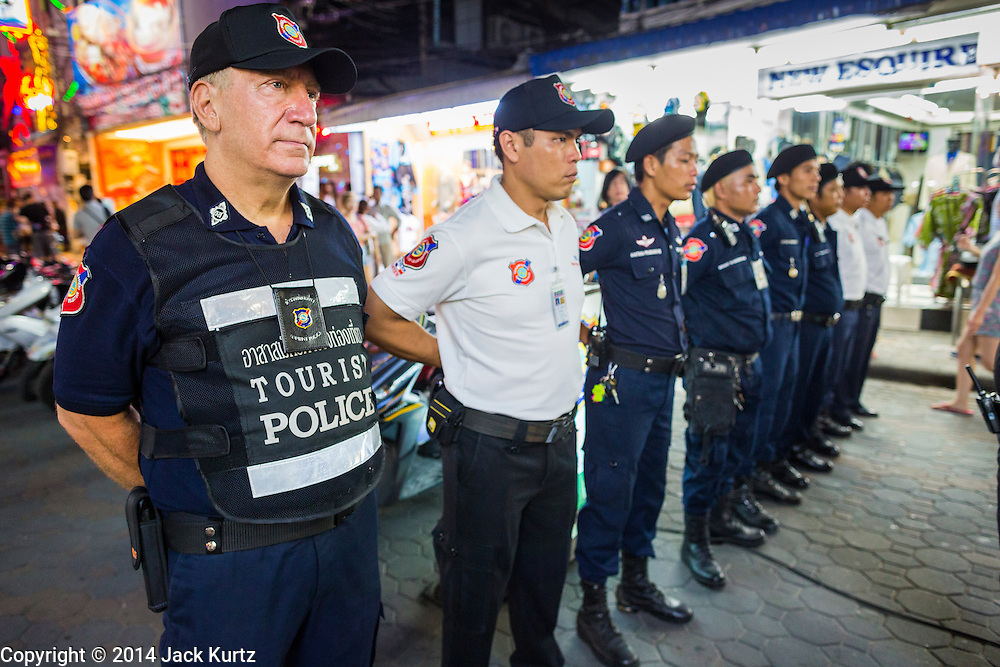 """26 SEPTEMBER 2014 - PATTAYA, CHONBURI, THAILAND: STEVE MANDALA, a volunteer with the Foreign Tourist Police Assistants (FTPA) falls into formation with other Tourist Police officers at the start of their shift on Walking Street in Pataya. Pataya, a beach resort about two hours from Bangkok, has wrestled with a reputation of having a high crime rate and being a haven for sex tourism. After the coup in May, the military government cracked down on other Thai beach resorts, notably Phuket and Hua Hin, putting military officers in charge of law enforcement and cleaning up unlicensed businesses that encroached on beaches. Pattaya city officials have launched their own crackdown and clean up in order to prevent a military crackdown. City officials have vowed to remake Pattaya as a """"family friendly"""" destination. City police and tourist police now patrol """"Walking Street,"""" Pattaya's notorious red light district, and officials are cracking down on unlicensed businesses on the beach.     PHOTO BY JACK KURTZ"""
