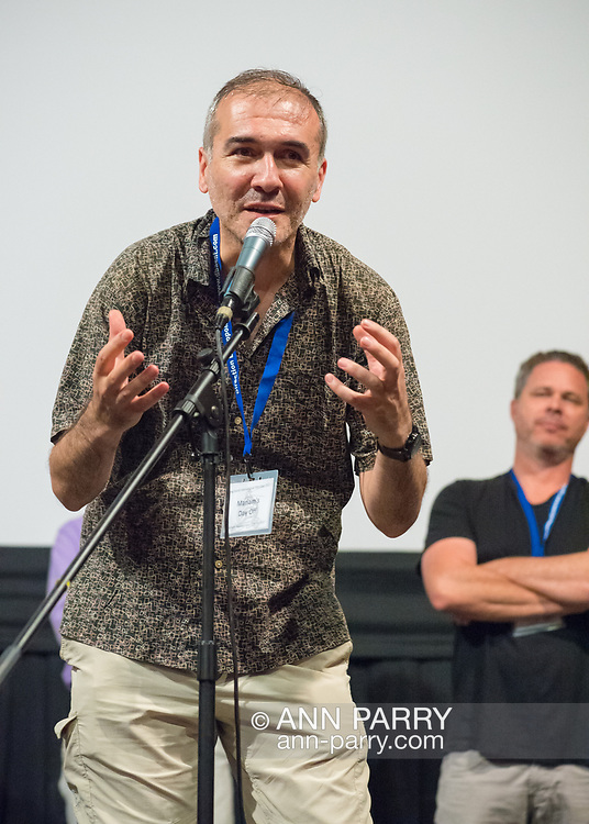 """Bellmore, New York, USA. 19th July 2017. Director and writer ARSHAK AMIRBEKYAN, at microphone, speaks during a Q&A at the Long Island International Film Expo LIIFE 2017. Screened earlier that evening was """"Mariam's Day Off"""" a short foreign film filmed in Armenia, about a young prostitue invited to an artists studio to model. Behind him at right is Director BRAD KUHLMAN."""