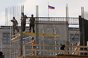 Moscow, Russia, 08/08/2006.&#xA;Builders  at work on scaffolding completely rebuilding the Moskva Hotel on Manezh Square beside the Kremlin. Behind them is the Russian State Duma, which still displays the Communist era hammer and sickle.<br />
