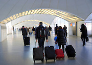 Blurred motion image of passengers pulling luggage bags along a bright corridor, Atocha railway station, Madrid, Spain