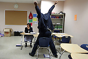 Jarrod Davis, right, stands up to put on his jacket after working in a small group with Teri Lynn Gilliam during Sherrie Lee Holden's 10th-grade World History class at Hampton Preparatory Academy in Dallas November 15, 2010.