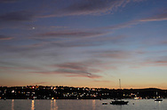 Beacon, New York -  Boats are anchored in the Hudson River after sunset on July 4, 2010. Lights from the city of Newburgh on in the background, and the planet Venus is visible in the sky at left. ©Tom Bushey / The Image Works