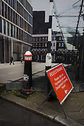 Crossrail construction hoarding of Smithfield scene placed alongside real street signs and bollard. The confusion of two images merge like a capriccio into one landscape as we see a background of corporate utopia with the dystopian foreground of a dirty street corner, affected by local construction site for the capital's Crossrail transport project.
