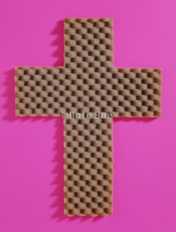 Packing foam in the form of a cross against a pink background.
