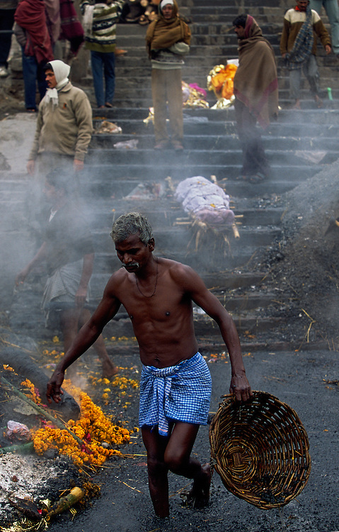 A Dom, an untouchable working at the cremation site, clearing the river Ganges from charcoal and other debris, while also looking for valuables, Manikarnika Ghat, the main cremation ghat of Varanasi, India. On the steps lie biers with dead bodies waiting to be cremated. To be cremated in the sacred city of Varanasi means a straight passage to heaven, many Hindus believe.