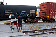 Two young men swaiting for a train to pass at a level crossing in New Orleans, Louisiana, USA. walking down the street in the French Quarter,