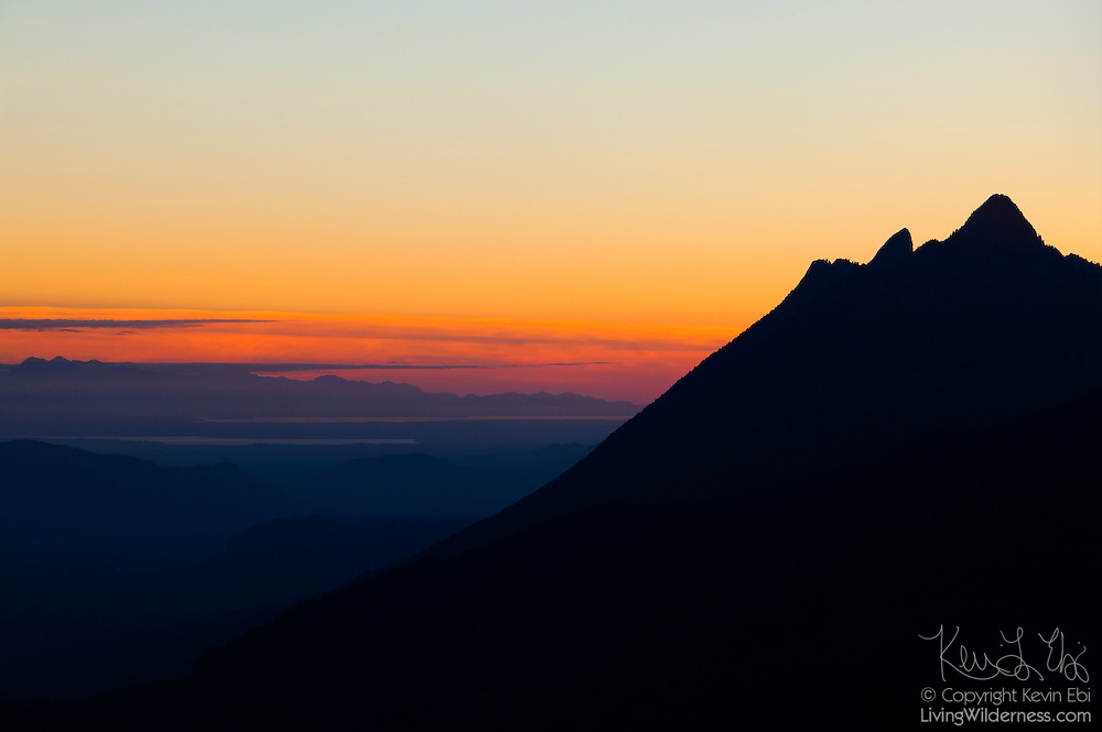 The peaks of Round Mountain and Mount Higgins, located near Darrington, Washington, are turned to silhouette at sunset in this view from the summit of North Mountain. The Olympic Mountains are visible in the background.