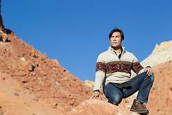 Asian American man on a rock formation in Abiquiu, New Mexico