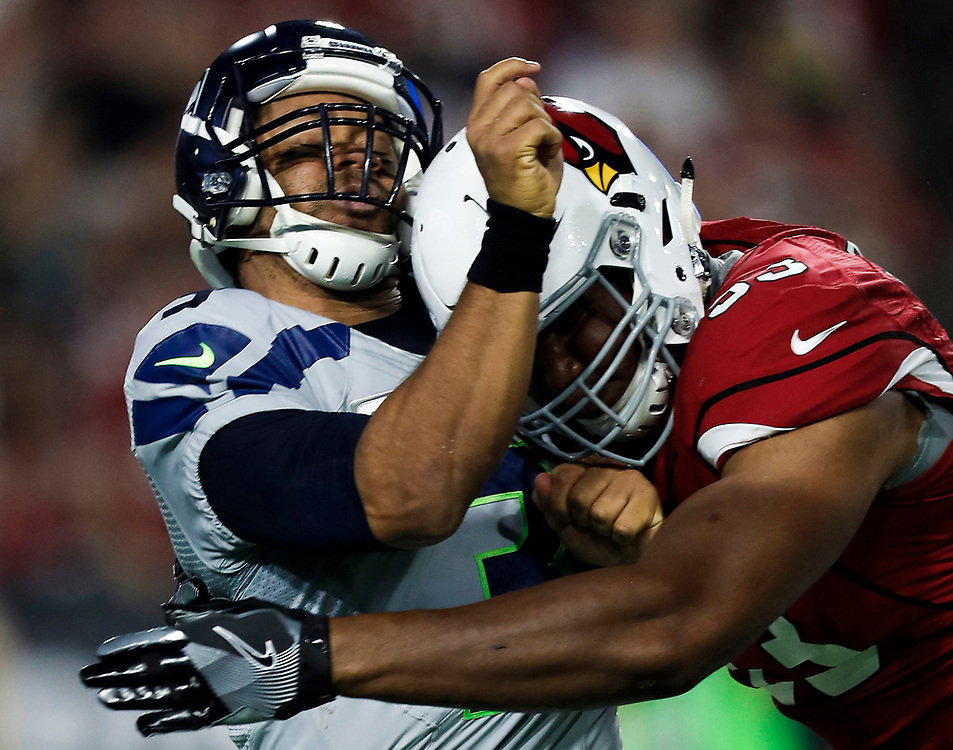 Seattle Seahawks quarterback Russell Wilson (3) gets hit by Arizona Cardinals defensive end Calais Campbell (93) during an NFL football game, Sunday, Oct. 23, 2016, in Glendale, Ariz. The Seahawks and Cardinals ended in overtime in a 6-6 tie. (Ryan Kang via AP)