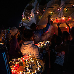 """The competing teams are playing traditional instruments and drums while brining their hot air balloon to the launching point to be eventually inflated by the fire of fuel-soaked """"torches"""".<br /> <br /> The fire balloons are made of paper, and designed by the participants. The candles, painting and even the fireworks are all made by hand. The making is quite an expensive affair, it often sums up to several thousand US Dollars. Parts of the funding is raised by the community and the rest by sponsorship from corporations.Together, the team is holding and rotating the balloon to show off the design. Some balloon makers focus on the design (painting or burmese script) whilst others adore them with candles called """"Sein Na Pan"""". The teams must work very quickly, because whilst the balloon steadily inflates and grows taller, many places to hang the candles quickly become out of reach. <br /> <br /> Meantime, the crowd waits in astonishment for the firework to explode. Usually there is 50 kilo pack of<br /> firework ajusted to the hot air balloons. After around 50 meters of altitude the firework starts<br /> launching, pointing in all directions – even downwards.<br /> <br /> Observing the hot air balloon rising high, over the full moon still shooting firework is a magical moment. And sometimes it turns into a deadly one... About a half-dozen deaths in the past few years along with dozens of injuries to be specific. Almost every year an accident takes place when a hot air balloon catches fire and drops<br /> away while the firework remains shooting mercilessly. Trays of candles in colored plastic holders with little hooks are brought out."""