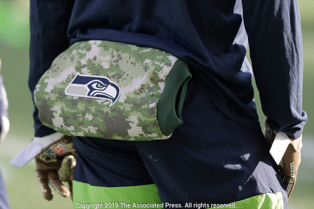 Seattle Seahawks quarterback Russell Wilson wears a camouflage hand warmer showing the Seahawks NFL football Salute to Service logo as he warms up before an NFL football game against the Tampa Bay Buccaneers, Sunday, Nov. 3, 2019, in Seattle. (AP Photo/John Froschauer)