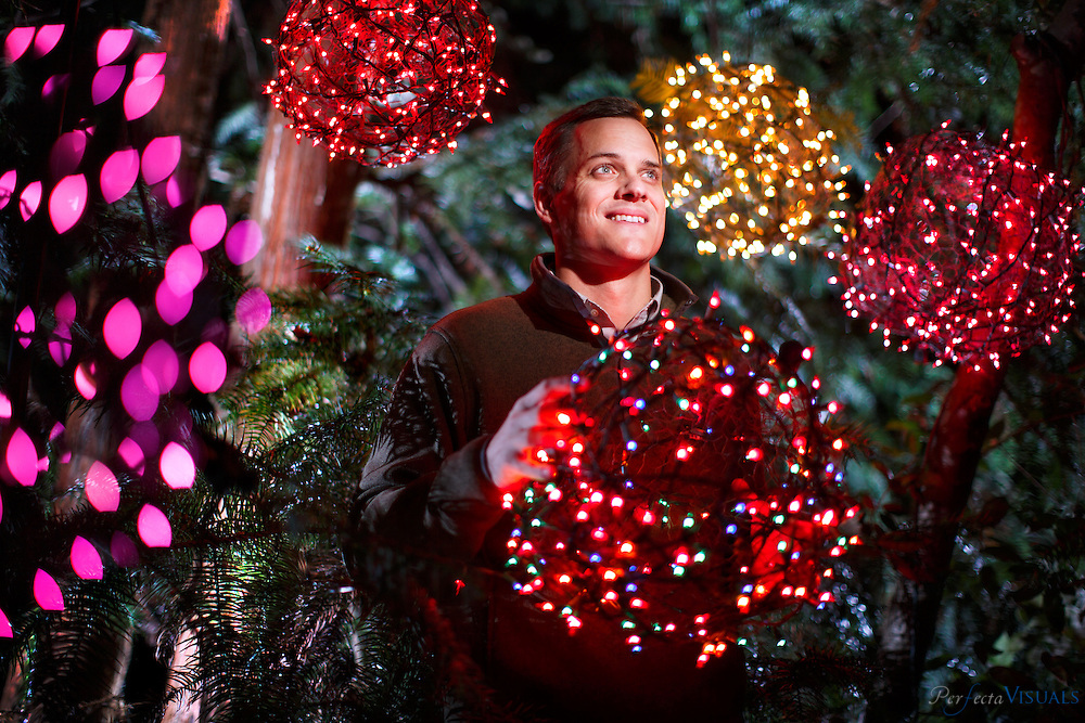 """Justin Smith with some of his """"tree ball"""" creations he and his family are known for on Tuesday, November 10, 2015, in Greensboro, N.C.<br /> <br /> JERRY WOLFORD and SCOTT MUTHERSBAUGH / Perfecta Visuals<br /> <br /> A teenage Justin Smith grinned with excitement as he launched the lighted Christmas balls his family crafted of chicken wire and colorful holiday lights high into the trees in his yard with his homemade potato gun.<br />  <br /> Over the next nineteen years, Justin helped his family's DIY project evolve into a community endeavor that would provide close to one million meals for the hungry.<br />  <br /> He praises his parents for showing him how to simultaneously help others, have fun and work hard.<br />  <br /> """"I have been able to see that this way of living is commonplace.""""<br />  <br /> As a financial planner, he helps people with their money.  <br />  <br /> As a mentor for youth leaders, he guides young males as they lead their communities.<br />  <br /> As a board member for Crescent Rotary, he lends a hand to people in need.<br />  <br /> Justin aims to raise his three children with the same sense of community that he was raised with.<br />  <br /> """"My hope is that my family and I create this environment of being selfless and being passionate for somebody else and my kids get to combine fun and community with doing something bigger."""""""