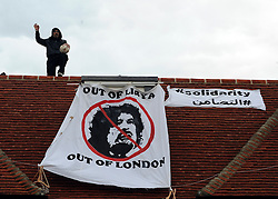 ©London News pictures. 09/03/11. A man on the roof. Squatters on the roof of a house belonging to the Gaddafi family in Hampstead today. Picture Credit should read Stephen Simpson/LNP