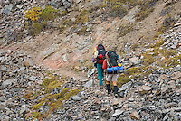 Backpackers traversing ridge above Grizzly Creek Valley, Tombstone Territorial Park Yukon Canada