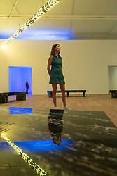 "© Licensed to London News Pictures. 20/07/2018. LONDON, UK. A staff member views ""FLOOR 2015"", a large scale kaleidoscopic work, by Jenny Holzer at the preview of ARTIST ROOMS: Jenny Holzer at Tate Modern. The annual free display includes text-based installations and paintings by the American artist Jenny Holzer and runs 23 July to summer 2019.  Photo credit: Stephen Chung/LNP"