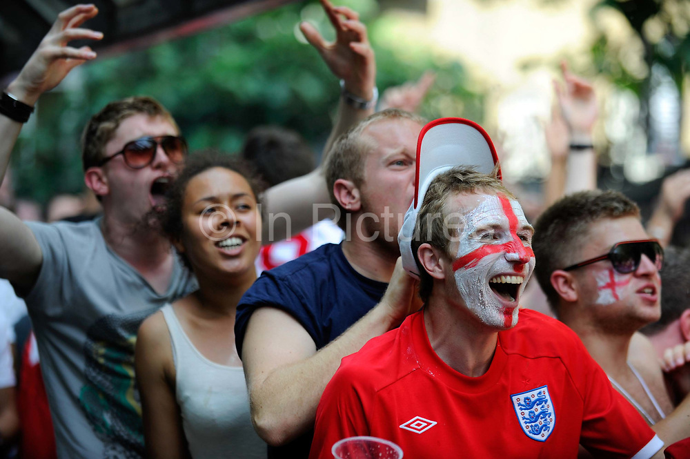 English football fans wearing England strip shirts watch England play Germany during the Fifa World Cup soccer tournament. Germany won the match 4-1.