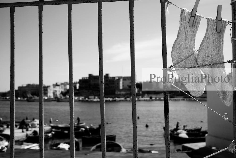 birndisi, villaggio pescatori. Bucato steso al sole con lo sfondo del porto.