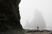 A man walks alone below large sea stacks at Rialto Beach, Olympic National Park, Washington.