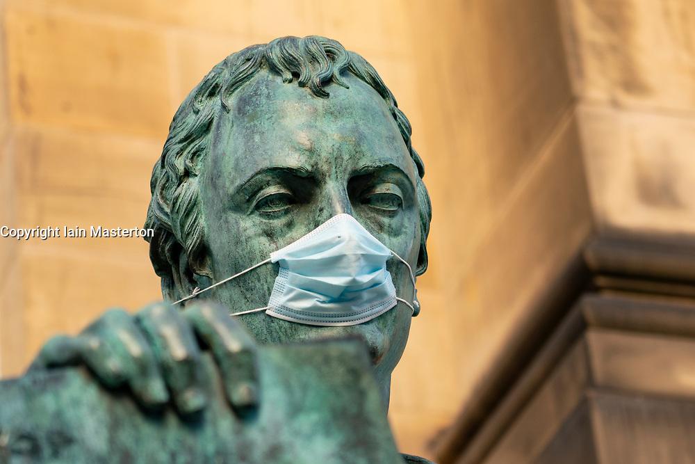 Statue of David Hume philosopher wearing facemask  on Royal Mile in Edinburgh, Scotland, UK