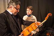 Luthier Gabriela Guadalajara shows a viola da Gamba to a show visitor.