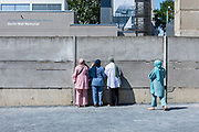 Visitors look through the tiles of the Berlin Wall, at the Berlin Wall Memorial site along Bernauer street in Berlin, Germany, August 12, 2021. The order for the start of the construction of the Berlin wall was issued on 13 August, 1961. The barrier which consists of roughly 43 kilometer of concrete wall, watch towers, check-points, barbed wire and mines, creating a border strip separating the former Western Allies' enclave of West Berlin, from the rest of the city under DDR control. The wall stood until the 9th of November, 1989.