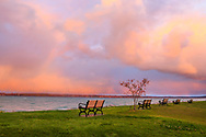 Benches and colorful storm clouds over Traverse Bay in early morning at Elk Rapids, Michigan, USA