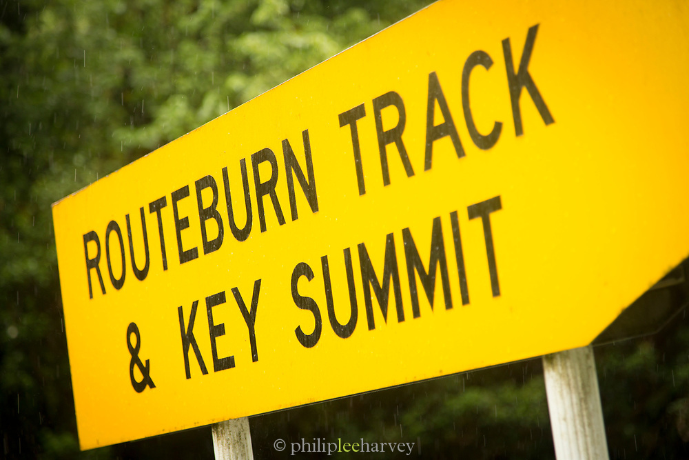 Yellow directional sign with black letters along Routeburn Track, South Island, New Zealand