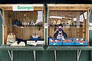 Duitsland, Nordrhein Westfalen, 1-5-2020 In Duitsland zijn in tegenstelling tot Nederland, mondkapjes verplicht in het openbaar vervoer en op plaatsen waar mensen te dicht bij elkaar kunnen komen. De jonge verkoper in deze kraam met asperges en aardbeien neemt geen risico . Foto: Flip Franssen