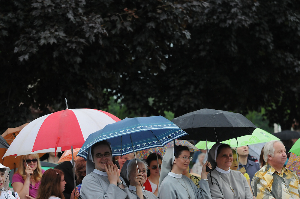 Attendees of a Memorial Day Field Mass seek cover from a light rain and threatening skies at St. Adalbert Cemetery in Niles.