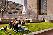 02 APRIL 2021 - MINNEAPOLIS, MINNESOTA: Protesters sit on a lawn in front of the Hennepin County Courthouse (in the background). Protesters are keeping a 24 hour presence in front of the Hennepin County Courthouse in Minneapolis during the murder trial of former Minneapolis Police Officer Derek Chauvin. Chauvin is on trial for murdering George Floyd in 2020. Floyd's death, while restrained and in police custody, set off a summer of racial justice protests across the United States.   PHOTO BY JACK KURTZ