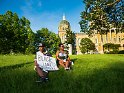 01 JUNE 2020 - DES MOINES, IOWA: An African-American couple sits on the lawn at the Iowa State Capitol. About 1,000 people gathered in front of the Iowa State Capitol in Des Moines Monday evening for a rally calling for racial justice. The rally was one week after George Floyd, an unarmed black man, was killed by a Minneapolis police officer who knelt on Floyd's back for more than eight minutes. There were protests  in Des Moines all weekend against Floyd's killing. There was some violence and some people have been arrested but the protests in Des Moines haven't been as serious as protests in other cities.          PHOTO BY JACK KURTZ
