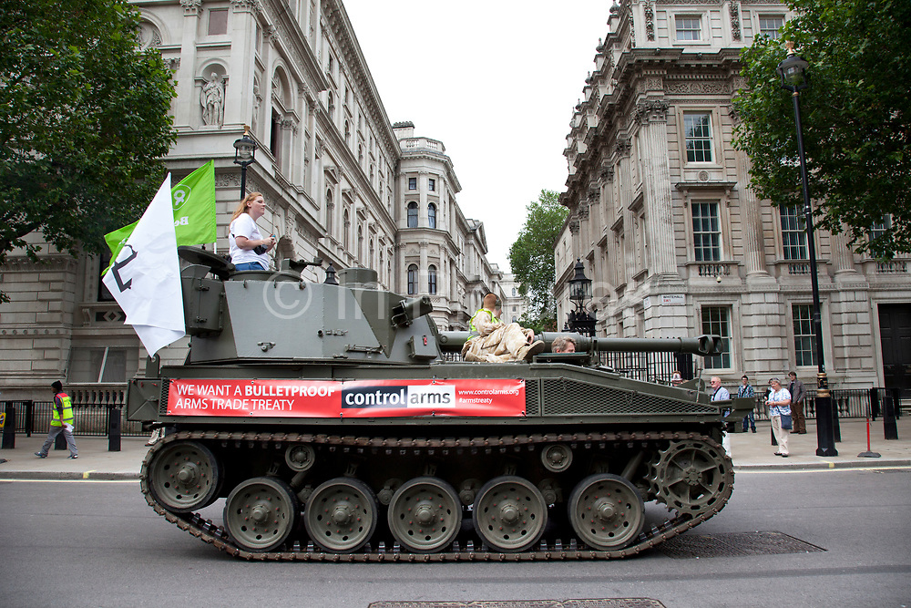 Tank Passing Downing Street on Whitehall. Campaigners and supporters from Oxfam and Amnesty International, as part of the Control Arms coalition, drive an Abbot gun tank around central London to highlight the need for a global Arms Trade Treaty (ATT) to be agreed during a United Nations conference next month (July 2012). London, England, UK. 27th June 2012.