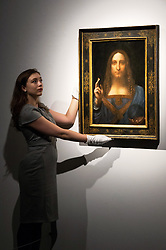 © Licensed to London News Pictures. 24/10/2017. London, UK. A Christie's staff member holds a painting titled Salvator Mundi (1490) by artist Leonardo da Vinci with an estimate in excess of 00 million. The painting of Christ as Salvator Mundi was recently attributed to Leonardo da Vinci, who is known to have painted the subject. It was lost and later rediscovered, and restored and exhibited in 2011. Photo credit: Ray Tang/LNP