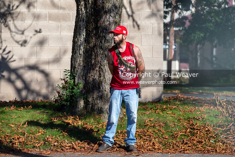 An armed man wearing a Make America Great Again hat watches a Black Lives Matter protest from a distance in Milton, Pennsylvania on September 20, 2020.