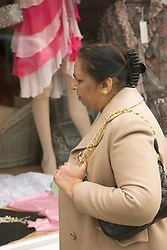 Older woman looking at dresses in a shop window,