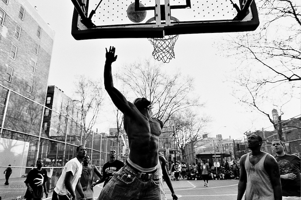 "April 18th 2008. New York, New York. United States..Located in the heart of Greenwich Village, the West 4th Street basketball Court, known as ""The Cage"", offers no seating but attracts the best players and a lot of spectators as soon as spring is around the corner..Half the size of a regular basketball court, it creates a fast, high level of play. The more people watch, the more intense the games get. « The Cage » is a free show. Amazing actions, insults and fights sometimes, create tensions among and inside the teams. The strongest impose their rules. Charisma is present..""The Cage"" is a microcosm. It's a meeting point for the African American street culture of New York. Often originally from Jamaica or other islands of the Caribbean, they hang out, talk, joke, laugh, comment the game, smoke… Whether they play or not, they're here, inside ""The Cage"". Everybody knows everybody, they all greet each other, they shake hands and hug: ""Yo, whasup man?"""