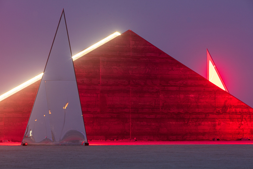 "Fragments, 2019 by: Marc Ippon de Ronda from: Paris, France year: 2019<br /> <br /> ""Fragments"" by French artist Marc Ippon de Ronda has been designed for Burning Man 2019. Where the artist turns an old Black Rock Desert legend into reality. The installation plays with the illusion of appearances and our ever-changing perception of self and surroundings, a recurring theme in de Ronda's work. During the day Burners see their reflections evolve inside the fragmented mirrors as they move through the sand winds and find shelter in its corners and covers. At sunrise and sunset the installation invites for meditation. Burners ascend and descend the central staircase experiencing a golden hue of warmth from the sun. At night, ""Fragments"" shifts again into abstract LED surfaces creating a magical apparition in the desert darkness. URL: https://fragmentsart.org Contact: contact@fragmentsart.org"