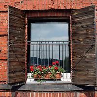 Europe, Scandinavia, Finland, Porvoo. Shutters and flowers adorn this brick facade building window in Porvoo.