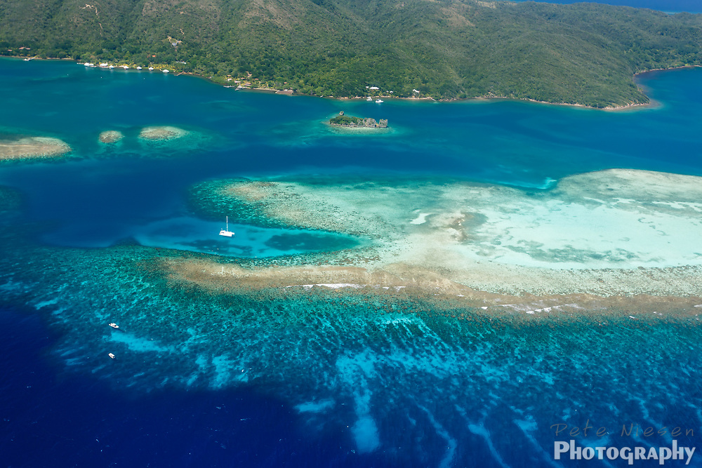 Aerial view of sailboat amid coral reefs surrounding tropical lush island