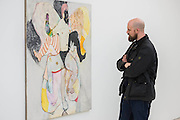 Ryan Mosley inspects one of his works  - PAINTERS' PAINTERS: Artists of today who inspire artists of tomorrow, featuring the work of nine present-day painters ranging from their 30s to their 60s at the Saatchi Gallery. There are nine artists included in the exhibition, whose aim is to start a discussion about the importance of painting and its future as a contemporary art form, given that installation, sculpture and video dominate the art world. The exhibition includes, Turner Prize nominee Dexter Dalwood whose paintings reimagine the lives of celebrities including Kurt Cobain, Brian Jones and Jackie Onassis, and  Norwegian Artist Bjarne Melgaard, the man behind the world's most controversial chair, Shropshire artist David Brian Smith, who uses his shepherd father as inspiration for his work and LA artist Raffi Kalenderian who helped found the band Wounded Lion. London 29 Nov 2016.