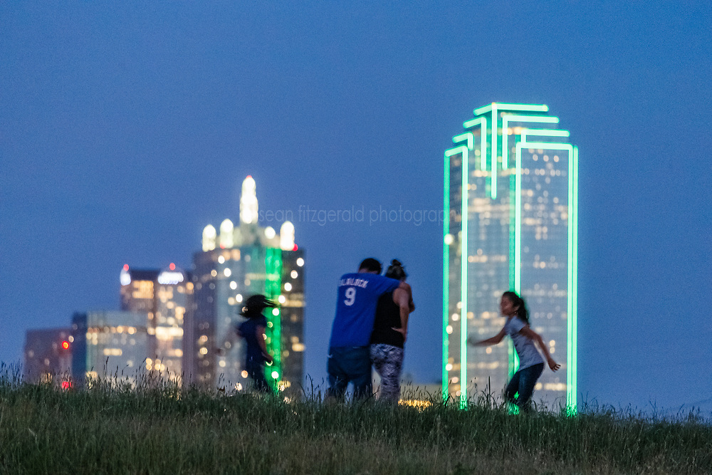 People walking on levee along Trinity River at night with downtown buildings in background,Dallas, Texas, USA