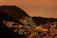Favelas (slums) seen at dusk, dot hillsides around Rio de Janeiro, Brazil.