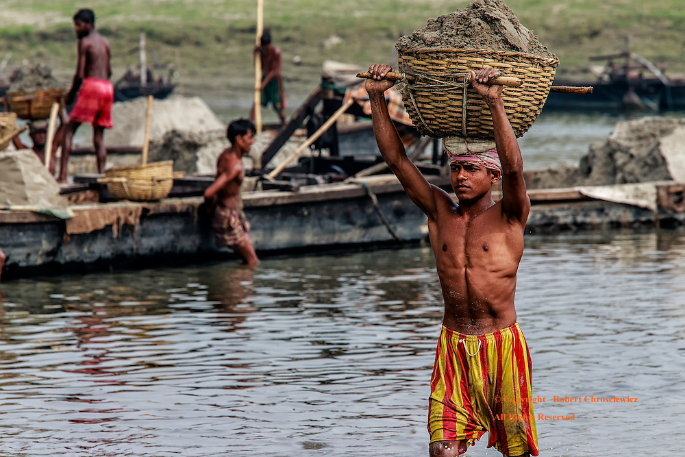 Slow and Steady: A young man carefully carries a heavy  basket of wet sand atop his head at the start of a long day on the Brahmaputra River, Mymensingh Bangladesh.
