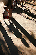 Children's shadows under a stilt home in the late afternoon. At the family home of Kruu, bush doctor, Larg Hoch, who sells her herbs and plants at Tbeang Meanchey market..Touth Koeun, an ex-Khmer Rouge child soldier turned midwife and trainer, is on the frontline again, but this time campaigning on maternity issues, in Preah Vihear province, Cambodia. The country experiences an extraordinarily high incidence of infant and maternal mortality. The Preah Vihear province, in Cambodia's north, bordering on the Thai border, can be described as an outback rural area, villages often many hours away from a health centre or clinic, and sometimes near the frontline where soldiers and their families are living. Here, Touth Kouen, a locally much respected pioneer and experienced in maternity issues, trains indigenous women, known as 'Traditional Birth Attendants' (TBA's), correct procedures to assist midwives and nurses, to give direct support to mothers and their babies, during ante and post natal periods. Traditional bush medicine and spiritual practices by 'Kruu' bush doctors, involving the killing of endangered species, gathering herbs and plants, whose burnt remains are often ground up into unhealthy potions, and fed to mothers as miracle cures, and postpartum heating, can cause illness and death. The Kruu, and local people in general need to be re-educated, so as to create a healthy nurturing environment for mothers and their babies. Preah Vihear Province, Cambodi