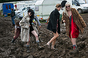 A group of festival goers in party outfits get stuck in mud ahead of the opening of the Glastonbury Festival 19th July 2016, Somerset, United Kingdom.  The Glastonbury Festival runs over 3 days and has 3000 acts, including music, art and performance and approx. 150.000 attend the anual event.