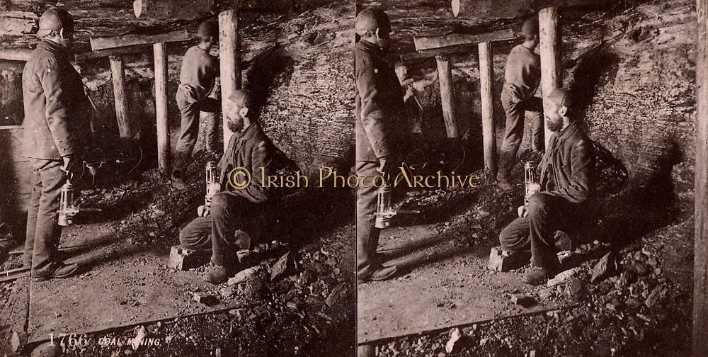 British coal mining - pitmen working a seam in a gallery with roof supported by wooden pit props. Photograph c1900.  Card for a stereoscope.