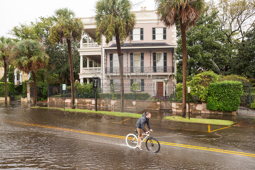 A bicyclist passes stately homes in floodwater along the Battery in the historic district as Hurricane Joaquin brings heavy rain, flooding and strong winds as it passes offshore October 4, 2015 in Charleston, South Carolina.