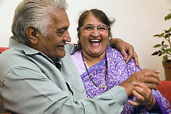 Older couple sitting on the sofa at home; smiling,